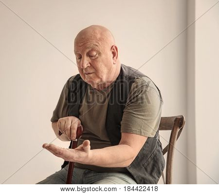 Senior man counting coins while sitting on chair in empty room. Poverty concept