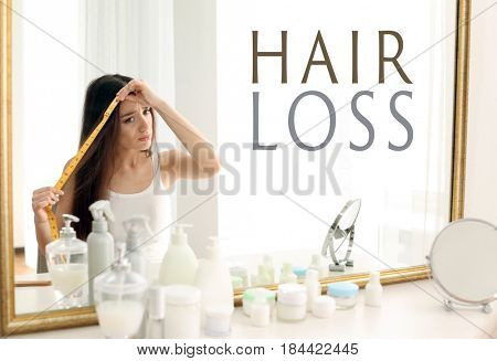 Hair loss concept. Young woman with measuring tape in front of mirror