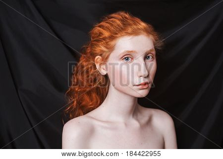 Fairy woman with long curly red hair gathered in ponytail on black background. Red-haired fairy girl with pale skin blue eyes unusual appearance without makeup. Natural fairy beauty. Fairy girl from the era of renaissance