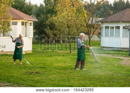 Man with garden hose. Couple of seniors outdoors. Jobs in horticulture.