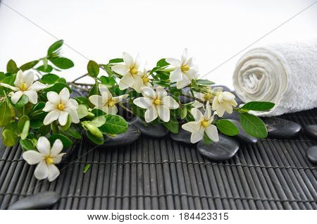 Branch gardenia with black stones,towel on mat background