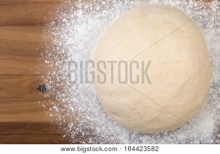 Ball A Dough And White Flour On A Wooden Cutting Board. Top View, Close Up.