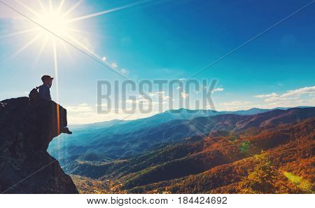 Man Sitting On The Edge Of A Cliff Overlooking