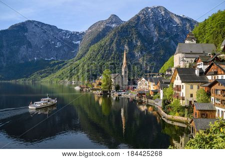 Beautiful View Of Hallstatt Lake And Town With Boat Arriving.