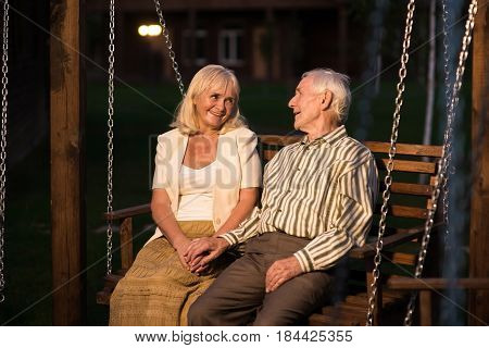 Couple of seniors, porch swing. Woman smiling to a man. Strong relationship tips.