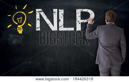 Businessman writes NLP on blackboard concept picture