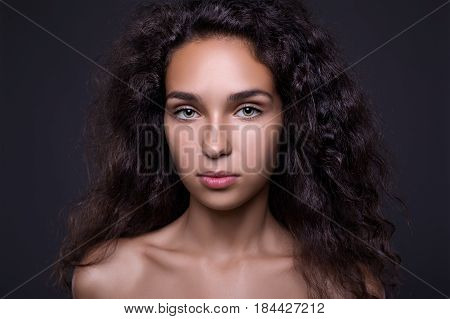 Closeup portrait of Beautiful brunette woman with long curly hair. Hairstyle beauty portrait on dark background.