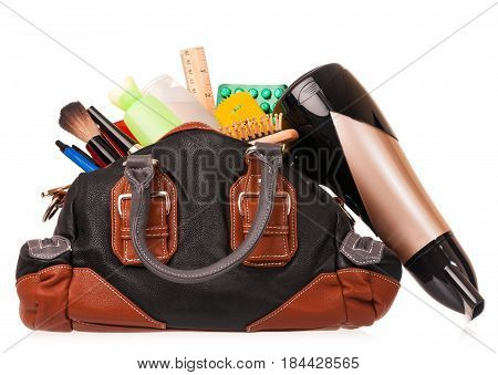 Overflowed woman handbag with accessories falls out isolated on white background