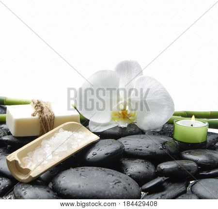 White orchid blossom with wet black stones ,grove, salt in bowl,soap  on wet background