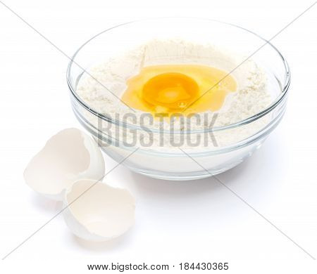 Flour with egg in glass bowl on white background