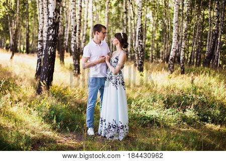 Beautiful people together. People in forest together. Girl with dark hair and brown eyes with a wreath on head in summer dress hugging a man together in a white shirt on a green background. Loving people in the forest on a sunny day together. People love