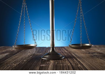 Scale of justice on old wooden table and blue background.  Law theme and concept.