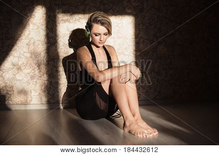 Lovely girl sit with tanned skin and white hair listening to music on headphones. Female beauty portrait of a beautiful makeup sit on floor. Girl sit and enjoying good music. Sit on laminate