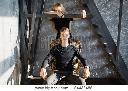 A young man and young blonde woman with long hair. Problems and difficulties in relations. Difficult situation in life. Conceptual photography. Actor play. Hard shadows. Show feelings. Hide feelings.