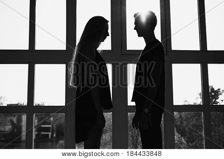 A young boy silhouette and girl silhouette with long blond hair standing in front of the window. Dancers silhouette during a workout. Problems and difficulties in relations. The difficult situation in life. Conceptual silhouette photography. Silhouette of
