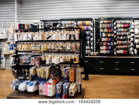 STRASBOURG FRANCE - APR 27 2017: Woman inside of Textile Tissue Fabric shop with multicolored and diverse accessories for sewing tools scissors and accessories and Cornice for curtains