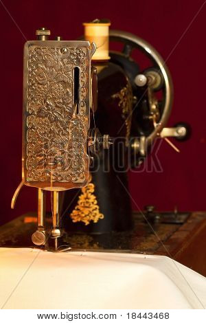 Old style sewing machine sewing a white cloth