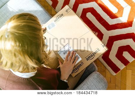 PARIS FRANCE - APR 24 2017: Curios woman unpacking unboxing large Amazon cardboard box with logotype printed on cardboard box side. Amazon Inc is the an American electronic e-commerce shopping company