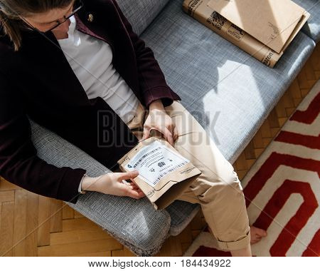 PARIS FRANCE - APR 24 2017: Multiple Amazon boxes woman unpacking unboxing Amazon cardboard box with logotype printed on cardboard box side. Amazon Inc is the an American electronic e-commerce shopping company