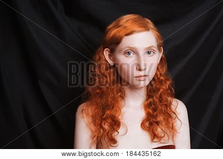 Woman with long curly red flowing hair on a black background. Red-haired girl with pale skin blue eyes bright unusual appearance without makeup. Natural beauty. The girl from the era of renaissance