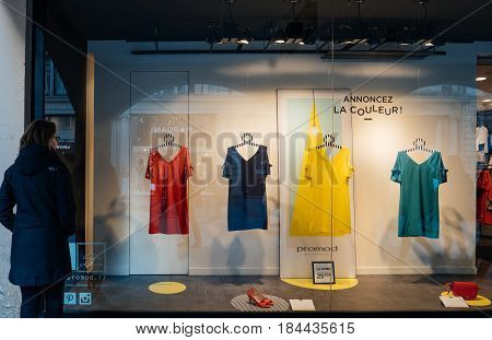 STRASBOURG, FRANCE - APR 27, 2017: young female woman customer admiring the Promod fashion clothing store with multi colored dresses in the vitrines illuminated by spotlight