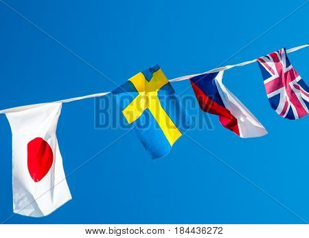 different national flags hanging on a rope on a blue sky background