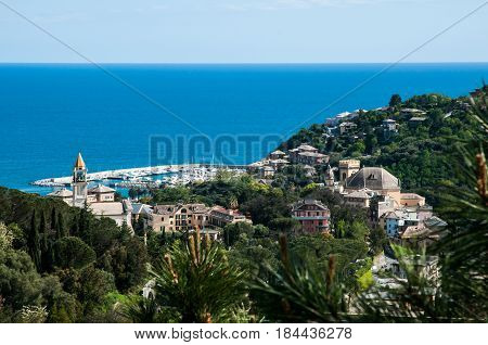 panorama of small town Arenzano in Liguria with its harbor and famous church 'Gesù Bambino di Praga' in the background