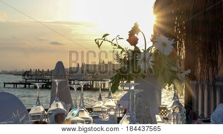 Luxury Table Setting On Pier At Sunset. Wedding reception place ready for guests.