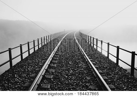 Railway bridge over a river in a foggy day.