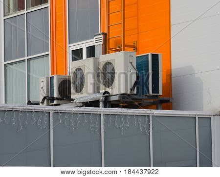 Set of air compressors installed on industrial building outdoors.