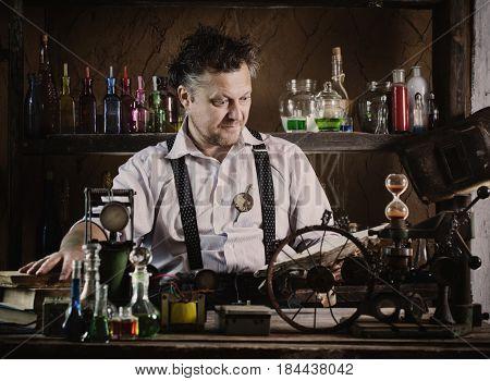 crazy medieval scientist reading book in his laboratory