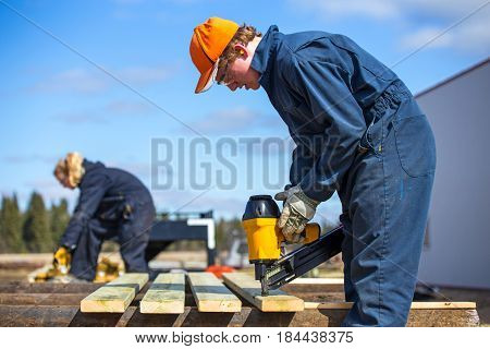 A teenage boy and a blurred teenage girl building outdoors with a power tool wearing protective industrial clothing