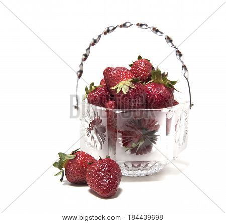 Strawberries in a crystal vase several pieces next to a vase on a white background