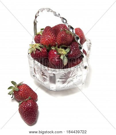 Strawberries in a crystal vase several pieces next to a vase on a white background. View from above