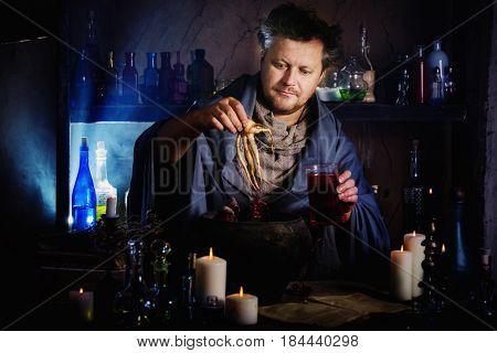 the wizard brews a potion at the table
