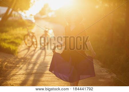 The girl in a blue hat and black dress with a backpack on her back in the backlit of sun sunlight. The sun light from the setting sun. Life style. Sun in nature. Summer sun