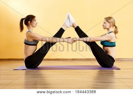 Two sports women doing yoga in gym