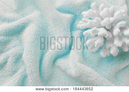 Beautiful white sea coral on the background of cotton terry blue towel crumpled by waves
