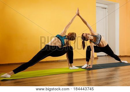 Two sportswomen doing stretching exercises in gym