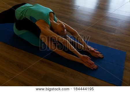 Photo of two young sportswomen in gym doing yoga