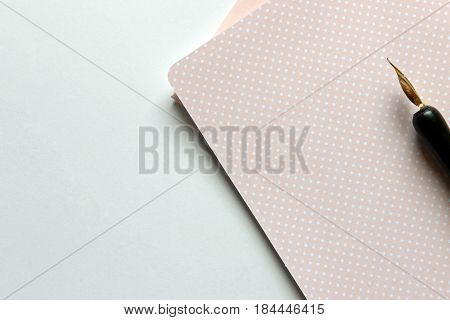 Pink polka dot stationary with calligraphy pen. Copy space