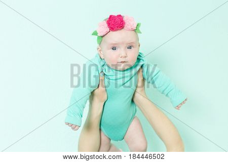 Portrait of a baby. Baby is held high above the mother's head.
