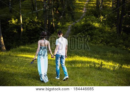 Beautiful people together. Couple in forest together. Girl with dark hair and brown eyes with a wreath on head in summer dress hugging a man together in a white shirt on a green background. Loving couple in the forest on a sunny day together. People love
