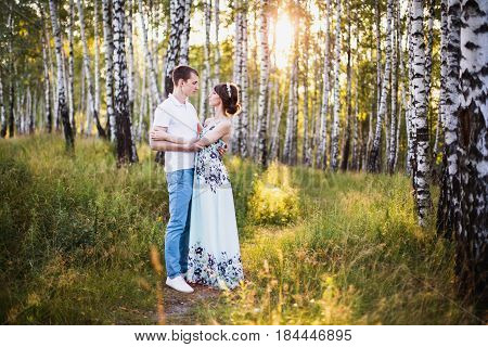 Beautiful love. Couple love in forest. Girl love with dark hair and brown eyes with a wreath on head in summer dress hugging a man in awhite shirt on a green background. Love couple in the forest on a sunny day. Couple love each other. Nice love. Love in