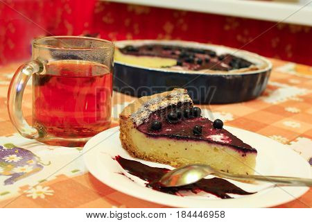 fresh pie with bilberry on the plate and cup of tea