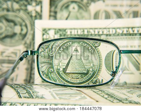 Glasses focused on dollar banknote dollar money with pyramid and eye detail