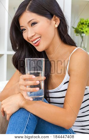 Beautiful Asian Chinese young woman or girl smiling with perfect teeth, relaxing and drinking a glass of water at home