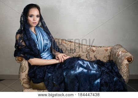 Young brunette in a blue silk dress and lace dark cape is sitting leaning on the armrest vintage sofa. Horizontal photo
