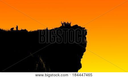 Black silhouette on orange and yellow background of group tourist standing arms outstretched happy with success on peak mountain near the cliff at Phu Chi Fa Viewpoint Chiang Rai Thailand