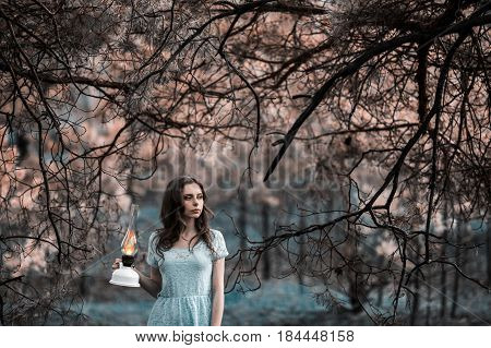 Very cute young girl with a kerosene lamp. Doll appearance. Woman with brown hair in a turquoise dress on scary nature. Long hair. Natural light. Model posing on the nature. Lamp in hand. Lost in scary forest. Scary tree. Scary mood